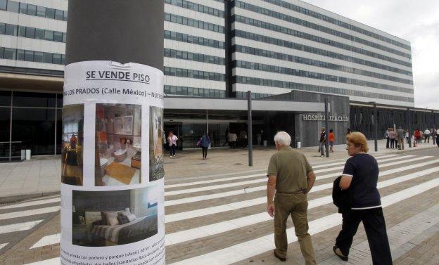 Un cartel anunciando la venta de un piso delante del Hospital Universitario Central de Asturias (HUCA).