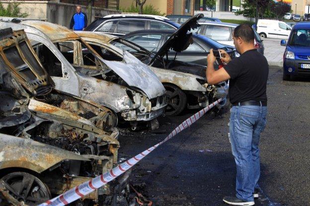 Uno de los vecinos saca una foto a los vehículos calcinados en el calle Anabel Santiago, situada en La Corredoria.