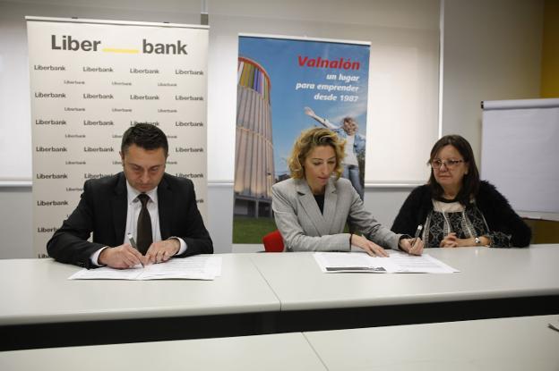 Laureano Calvo, de Liberbank y Ana Concejo y Marta Pérez, de Valnalón, en la firma del convenio para la financiación de la actividad de 175 cooperativas escolares. / JUAN CARLOS ROMÁN