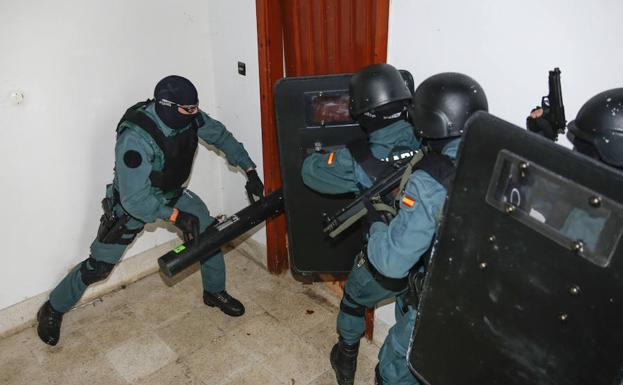 Los miembros de la URO derriban una puerta para acceder al piso.