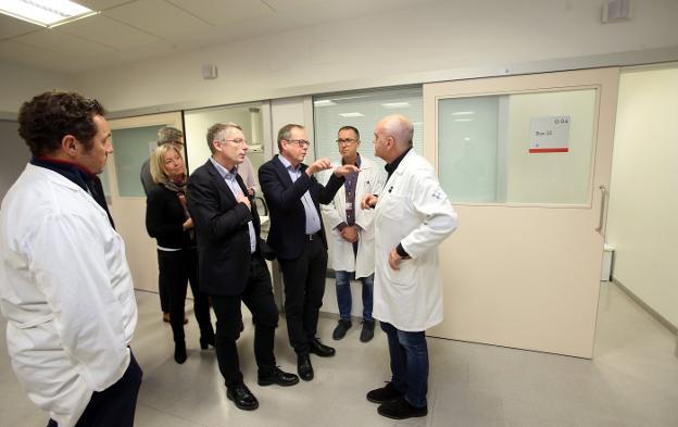 El director y el gerente del HUCA, Pablo Fernández y Luis Hevia (ambos con bata) charlan con la delegación sueca. / ÁLEX PIÑA