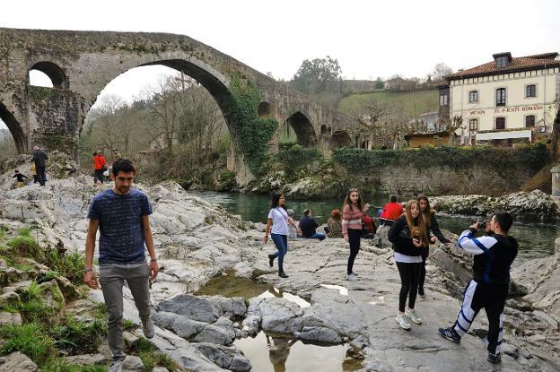 Varios turistas disfrutan del Puente Romano de Cangas de Onís aprovechando el buen tiempo. / X. CUETO